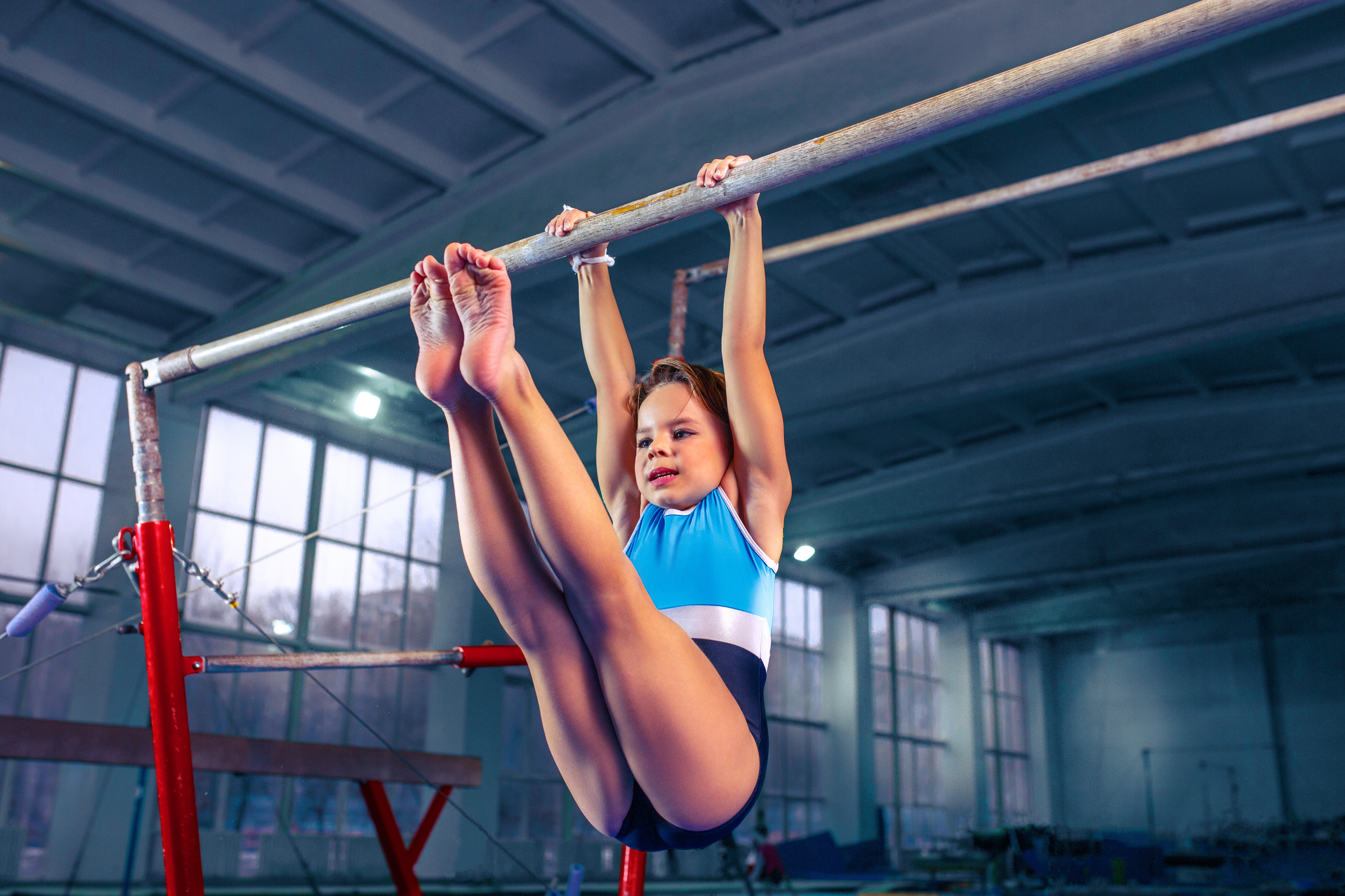 beautiful girl is engaged in sports gymnastics on a parallel bars